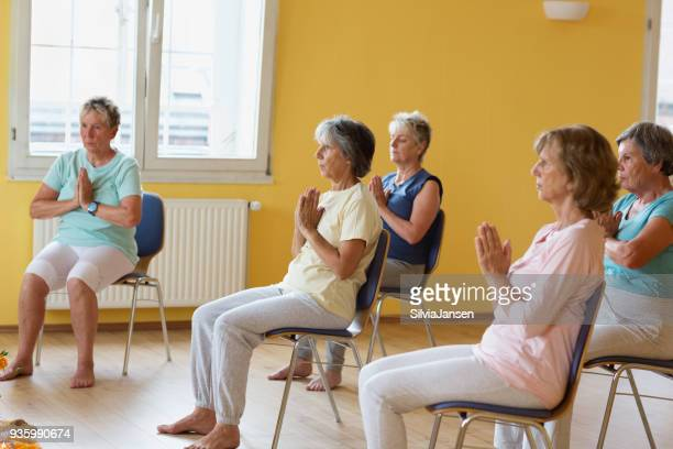 active senior women in yoga class exercisig on chairs - chair stock pictures, royalty-free photos & images