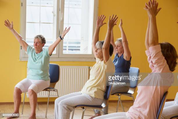 actieve senior vrouwen in yoga klasse exercisig op stoelen