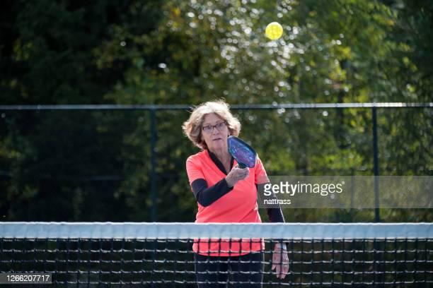 actieve hogere vrouwen die pickleball bij een openbaar hof spelen - racket sport stockfoto's en -beelden