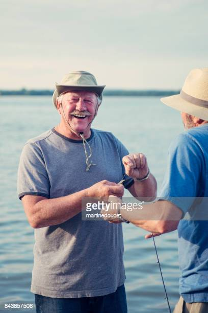 active seniors brothers on a fishing trip. - brother stock pictures, royalty-free photos & images