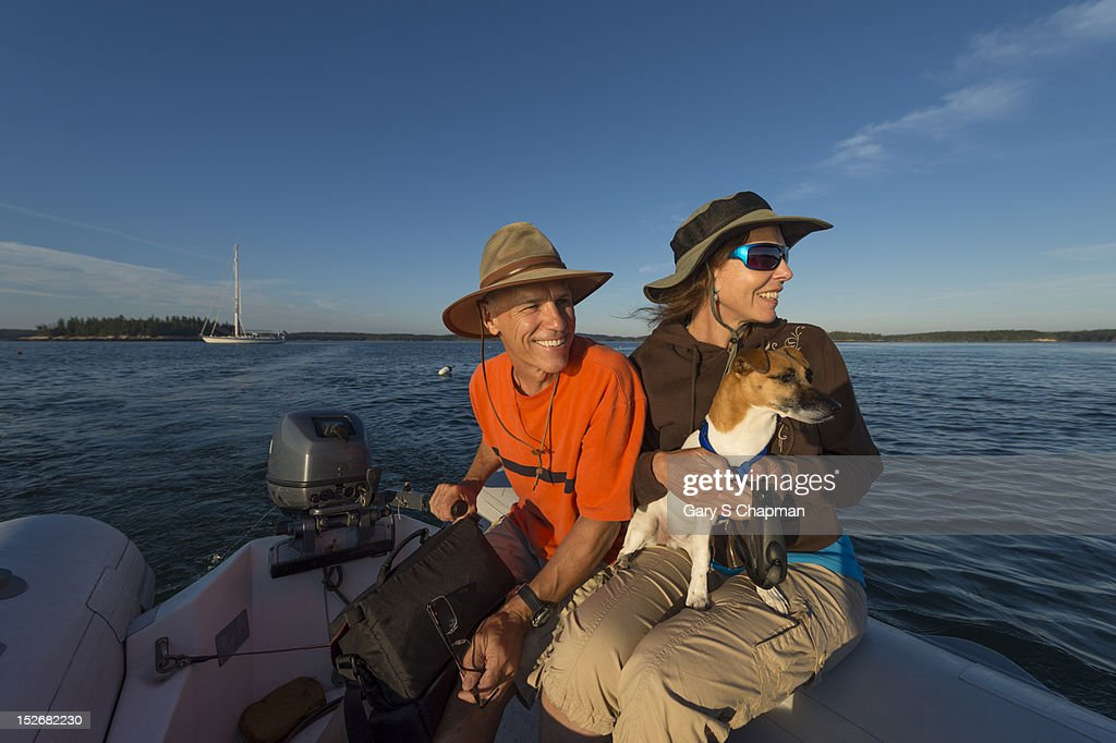Active seniors dinghy to shore from sailboat : Stock Photo