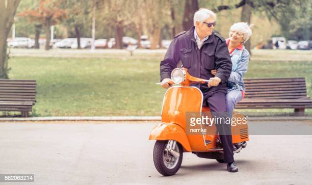 active seniors driving motorbike together - prosperity stock photos and pictures
