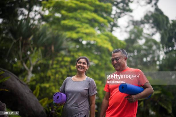 active seniors enjoying a healthy lifestyle - indian couples stock pictures, royalty-free photos & images