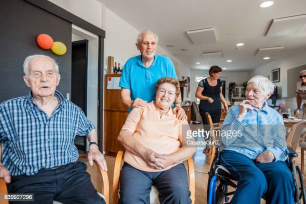 active seniors exercising together in an elderly daycare center - retirement community stock pictures, royalty-free photos & images
