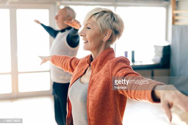 active seniors in fitness class stretching arms - good posture stock pictures, royalty-free photos & images