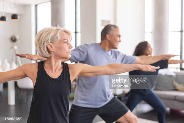 active seniors in group fitness class - baby boomer stock pictures, royalty-free photos & images