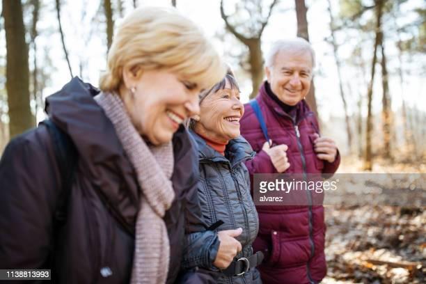 actieve senioren op land wandeling - wandelen lichaamsbeweging stockfoto's en -beelden