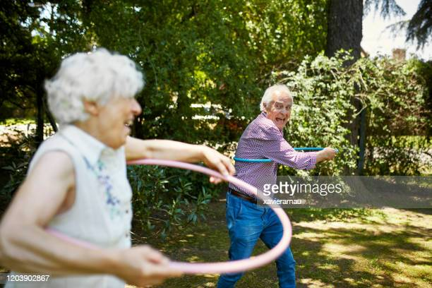 actieve senioren swingende hoepels in buenos aires backyard - friendly match stockfoto's en -beelden