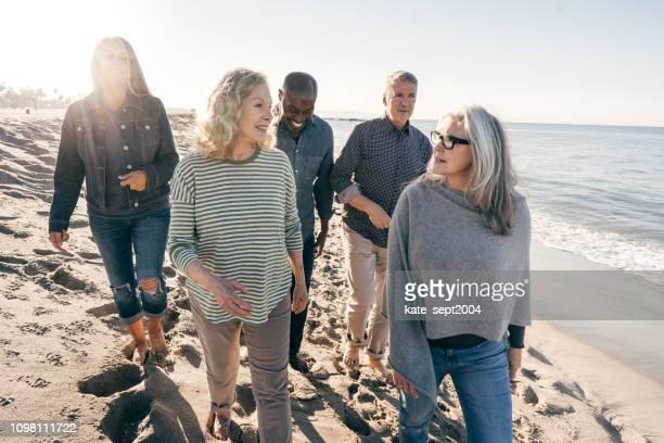 aktive senioren wandern am strand - 65 69 jahre stock-fotos und bilder