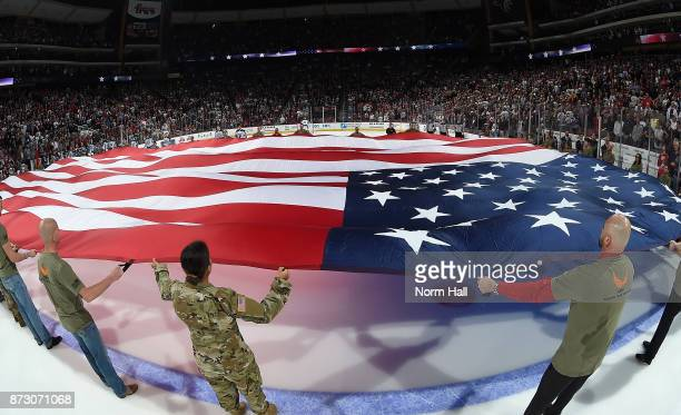 Active service men and women hold a large american flag over the ice before the start of a game between the Arizona Coyotes and Winnipeg Jets as part...