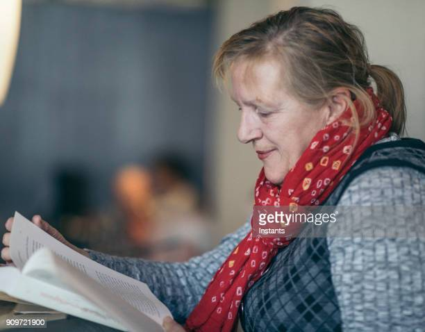active sixty year old woman reading a textbook in a café. - 63 year old female stock pictures, royalty-free photos & images