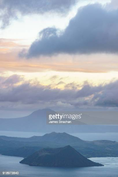 active taal volcano at dusk in the middle of lake taal, itself the result of eruptions over 100,000 years ago, tagaytay, luzon island, philippines - taal volcano stock photos and pictures