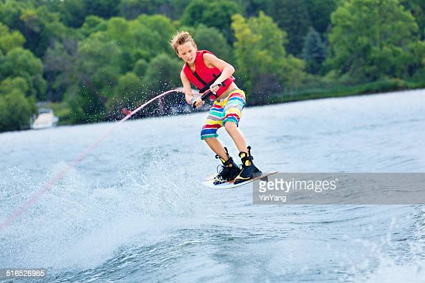 active teen boy water ski boarding on lake in summer - waterskiing stock photos and pictures