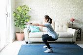 Active woman doing squats at home