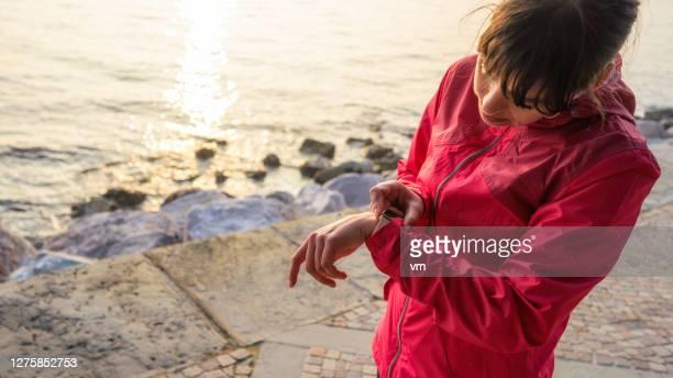 active woman looking at her smart watch - quebra ventos imagens e fotografias de stock