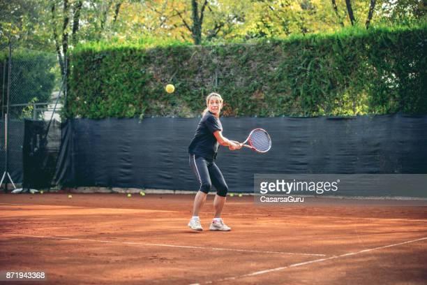 Femme active, jouer au Tennis dans un Court de Tennis extérieur