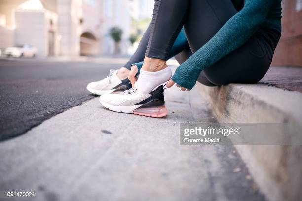active woman putting her sneaker on while sitting on a street sidewalk - sports footwear stock pictures, royalty-free photos & images