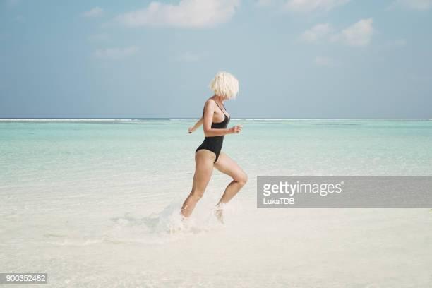 Aktive Frau läuft durch Ozean, Malediven