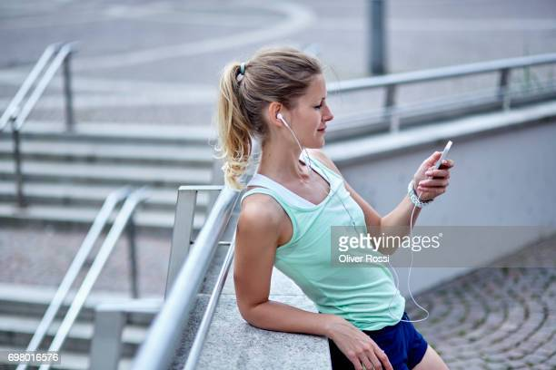 active woman with earbuds and cell phone taking a break - riposarsi foto e immagini stock