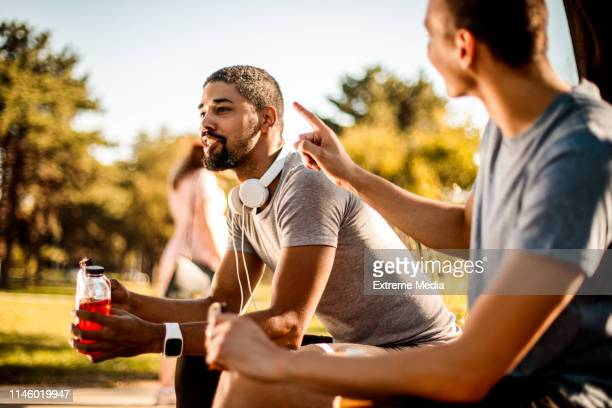 aktive junge männer genießen einen proteinstange, der sich beim sportgetränk mit sportgetränken versorgt, während sie sich ausruhen und mit seinem freund in einem öffentlichen park sprechen. - energydrink stock-fotos und bilder