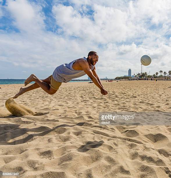 active young man jumping while playing beach volleyball - beach volleyball stock pictures, royalty-free photos & images