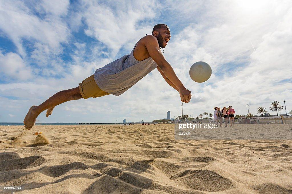 Aktiver junger Mann springt beim Beachvolleyball : Stock-Foto