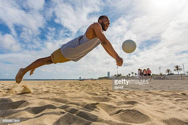 active young man jumping while playing beach volleyball - beachvolleybal stockfoto's en -beelden