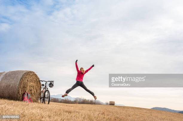 Aktiv ung kvinna utövar på platån nära hö boll