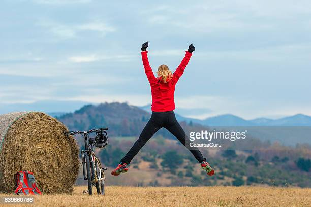 Active Young Woman Jumping on the Field