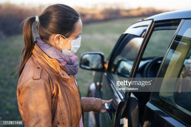 active young woman taking her car to go to work. driving with a protective mask on the face. - driving mask stock pictures, royalty-free photos & images