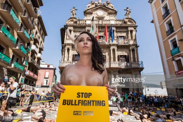 Activist against animal cruelty holds a banner anti bullfightings during a performance before the San Fermin celebrations in the main square of...