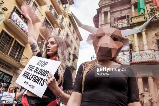 Activist against animal cruelty in bull fightings wears a paperboard bullhead mask before the San Fermin celebrations Spain Banner says quotstop...