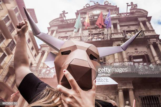 Activist against animal cruelty in bull fightings wears a paperboard bullhead mask under the Pamplona city council building Spain before the San...