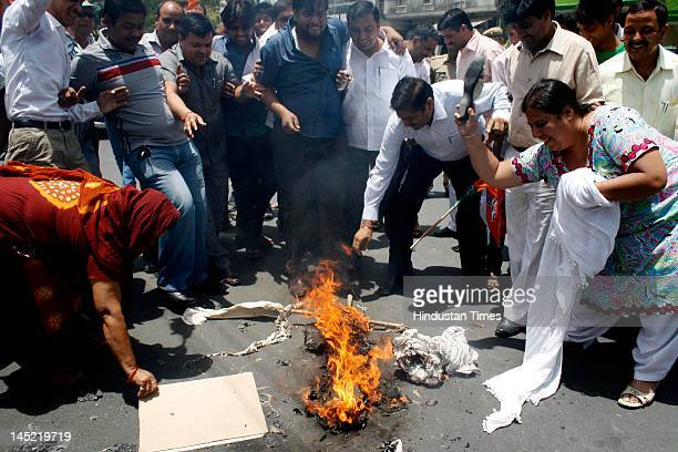 Activist aims to hit an burnt effigy during a protest rally against recent petrol hike at Sector 22 on May 24, 2012 in Noida, India. Activists...