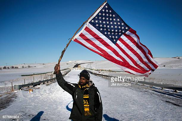 Activist and school teacher Lend Frison from Omaha, Nebraska, holds an American flag as he stands by a police barricade on a bridge near Oceti...