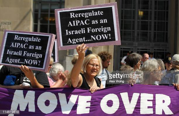 Activist Ann Wright of Code Pink holds up a sign as she protests against the American Israel Public Affairs Committee outside Department of Justice...