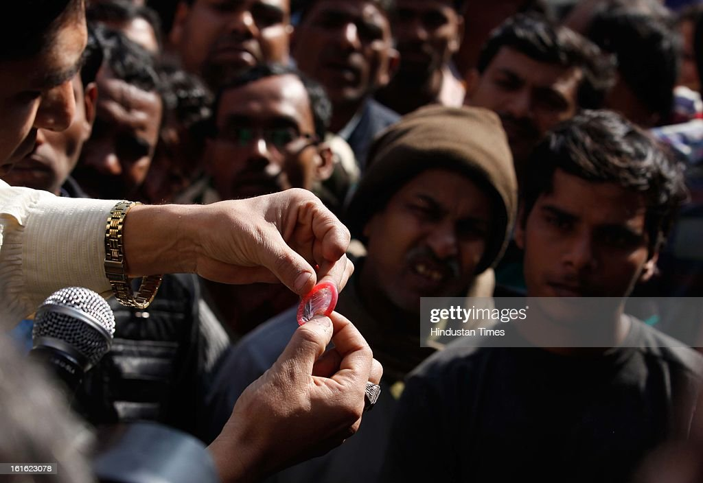 activist demonstrates how to use a condom to spread safe sex awareness at G B Road on the occasion of International Condom Day on February 13, 2013 in New Delhi, India. AIDS Healthcare Foundation (AHF) organised a 'Safe Sex Awareness' event in the Indian capital to promote the use of condom to prevent spread of HIV infections and sexually transmitted diseases.