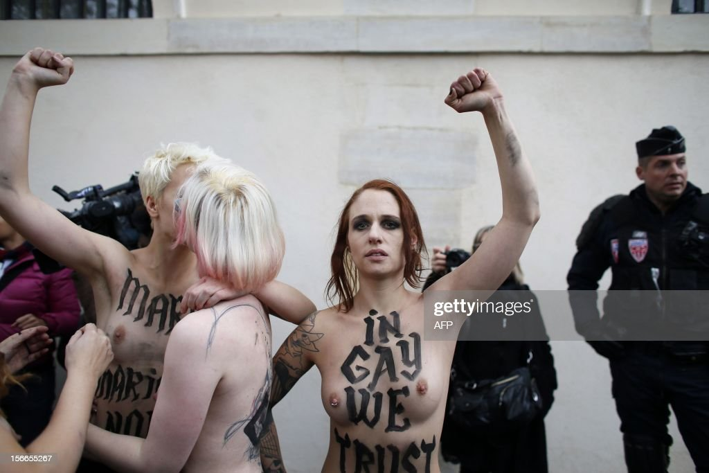 Activist Eloïse Bouton and Topless activists of the Ukrainian women movement Femen raise fist during a protest against the fierce opposition from the Roman Catholic Church to authorise gay marriage on November 18, 2012 in Paris.