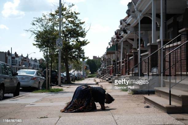 """Activist Erricka Bridgeford of Baltimore Ceasefire prays as she participates in a """"sacred space"""" ritual near where a person was recently murdered on..."""