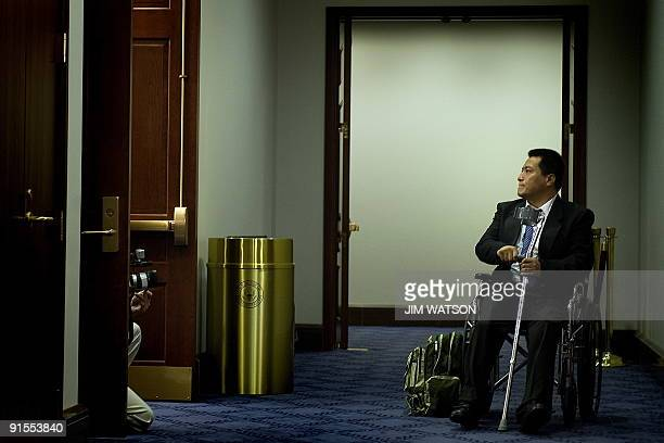 Activist Fang Zheng who lost his legs 20 years ago in Beijing's Tiananmen Square demonstration for democratic rights waits in the hall wall as he...
