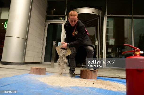A activist from Extinction Rebellion pours wood ash onto sheeting during a protest action to challenge BlackRock as a main player driving...