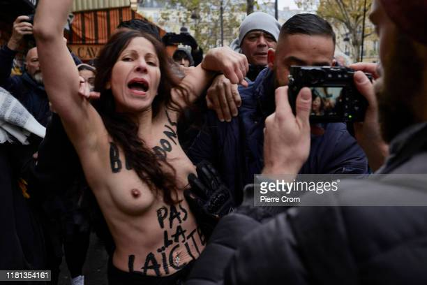Activist from the feminist group Femen protesting for a secular society is carried away as an estimated of ten thousand French citizens march from...