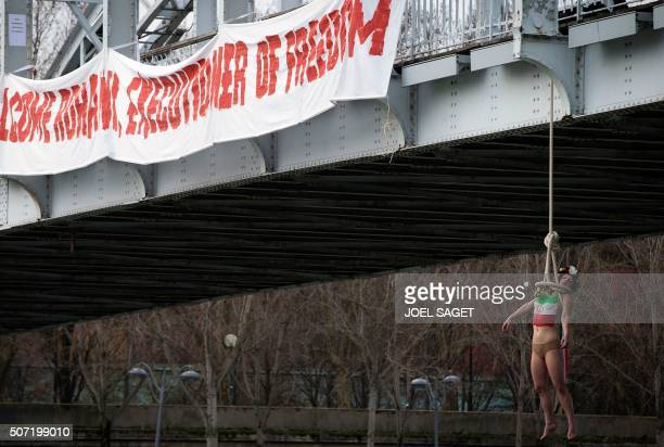 A FEMEN activist hangs from a mock noose during a protest in Paris against the visit of the Iranian president on January 28 2016 Iranian President...