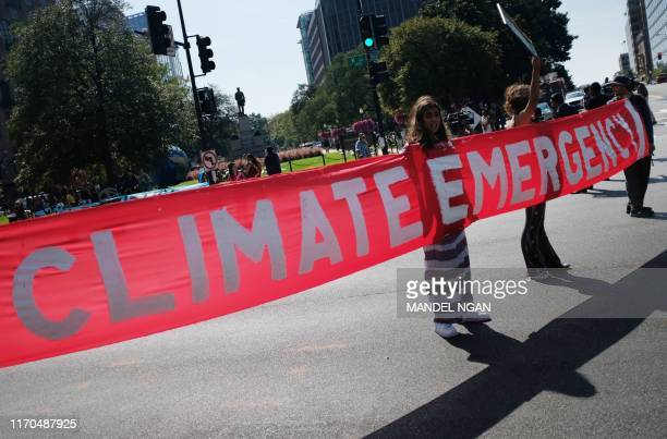 TOPSHOT Activist hold a banner while blocking a major intersection during climate protests in Washington DC on September 23 2019 Some 60 world...
