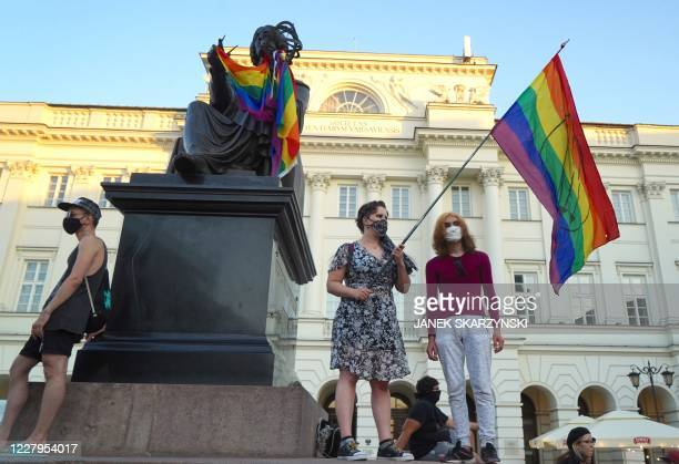 Activist holding a rainbow flag stands on the monument of Copernicus in Warsaw, Poland, on August 7, 2020. - Polish police arrested a gay rights...