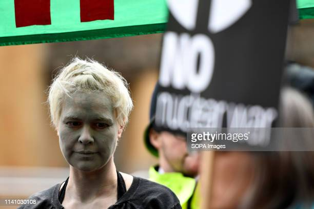 Activist is seen with her face covered with ash during the protest Antinuclear activists gathered opposite Westminster Abbey in London to protest...