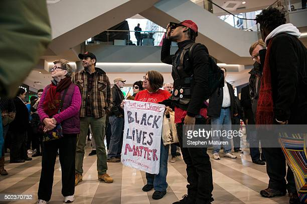 Activist Jess Sundin holds a sign that reads 'BLACK LIVES MATTER' in the rotunda of the Mall of America on December 23 2015 in Bloomington Minnesota...