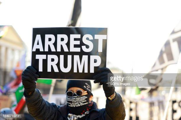 """Activist Laurie Arbeiter holds a sign reading """"Arrest Trump"""" at Black Lives Matter Plaza after the departure of Donald J. Trumps helicopter at the..."""