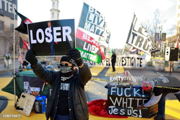"""Activist Laurie Arbeiter holds a sign reading """"Loser"""" at Black Lives Matter Plaza after the departure of Donald J. Trumps helicopter at the white..."""