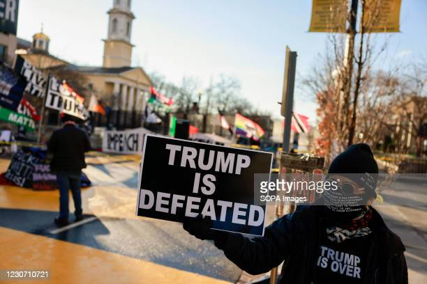 """Activist Laurie Arbeiter holds a sign reading, """"Trump is Defeated"""" at Black Lives Matter Plaza after the departure of Donald J. Trumps helicopter at..."""